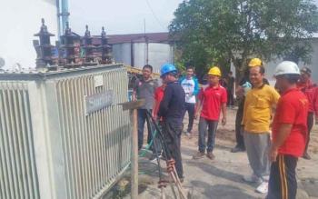 Analis Kinerja PT PLN Rayon Pangkalan Bun, Suprapto (dua kanan) saat membersihkan peralatan di PLTD Pangkalan Bun untuk persiapan kedatangan 13 mesin pembangkit listrik tenaga diesel, Jumat (10/3/2017).