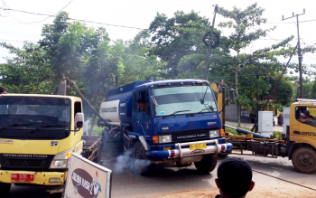 Dua buah mobil gerek sedang berusaha menarik truk tangki yang terbalik di Jalan Tidar, Kecamatan Baamang, Kotawaringin Timur, Jumat (10/3/2017).