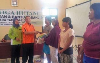 Kepala BPBD Kobar, Hermon F Lion menyerahkan bantuan berupa beras dari PT Korintiga Hutani kepada salah satu korban banjir Aruta, Sabtu (11/3/2017).