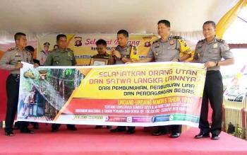 Kapolres Kapuas bersama Polsek Kapuas Hulu membentangkan spanduk sosialisasi perlindungan orangutan