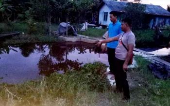 Sejumlah warga dan aparat kepolisian saat memeriksa tempat ditemukannya jasad korban tenggelam.