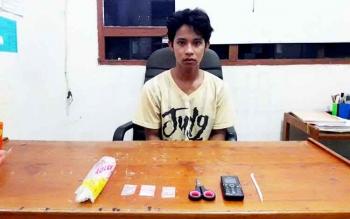 Syukur duduk di depan barang bukti sabu miliknya saat berada di Polres Kotim.