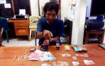 Fery, pengedar sabu menunjukkan barang bukti yang berhasil diamankan polisi.