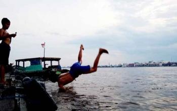 Anak tengah bermain di Sungai Mentaya, Sampit.