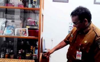Kepala Dinas Perindustrian dan Perdagangan Kota Palangka Raya Aratuni D Djaban menunjukkan contoh minuman keras yang disimpan di ruang kerjanya, Senin (13/3/2017).