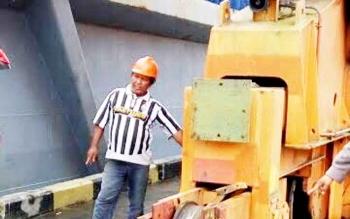 Seorang pekerja sedang menunjukkan crane yang menabrak motor para karyawan bungkar muat di pelabuhan tersebut.