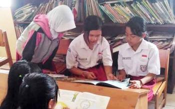 Sejumlah murid sekolah dasar membaca buku di Kantor Dinas Perpustakaan dan Kearsipan Kabupaten Gunung Mas.