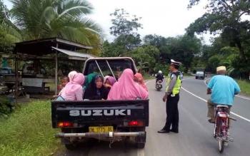 Pengemudi pikap ditegur polisi karena angkutan barang ini membawa penumpang.\r\n