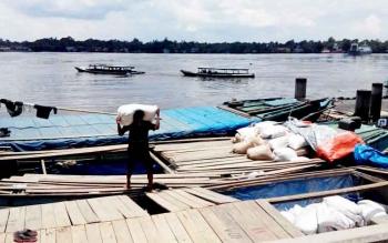Seorang pekerja sedang mengangkat karung beras Pagatan, saat tambat di Dermaga Habaring Hurung.