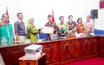 Komisioner KPU Kabupaten Barito Selatan Nining Kurningsih menyerahkan hasil pleno penetapan bupati dan wakil bupati terpilih kepada ketua DPRD Barsel Tamarzam. Jumat (17/3/2017).