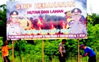Anggota Polsek Dusun Selatan, Kabupaten Barito Selatan, memasang spanduk imbauan dan larangan membakar hutan dan lahan.