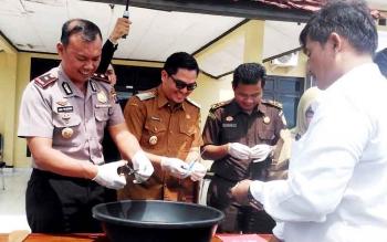 Wakil Kapolres Gumas Kompol Qori Wicaksono didampingi kepala BNN Gumas Rony Karlos dan pejabat lainnya memusnahkan sabu, Senin(20/3/2017)