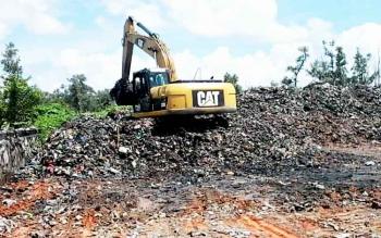 Sebuah alat berat tampak memindahkan tumpukan sampah di areal TPA Kasongan, Senin (20/3/2017)