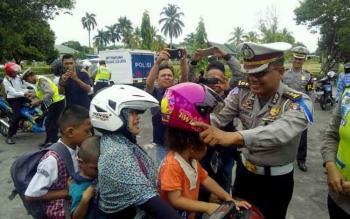 Kabag Bin Ops Ditlantas Polda Kalteng AKBP Andhika Wiratama memakaikan helm kepada anak yang dibonceng ibunya, Selasa (21/3/2017).