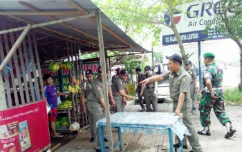 Petugas Satpol PP Kota Palangka Raya menertibkan tempat berjualan milik pedagang di Jalan Yos Sudarso, Selasa (21/3/2017)