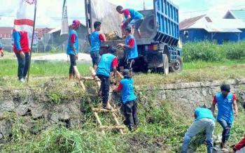 Beberapa peserta sedang mengangkat lumpur atau sampah ke truk saat mengikuti lomba