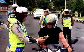 Anggota Satlantas Polres Sukamara saat memberikan bingkisan sembako kepada pengendara yang patuh dalam berlalu-lintas.