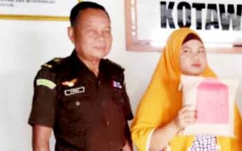 Wahidah tersangka kasus zenith didampingi petugas Kejaksaan, Rabu (22/3/2017)