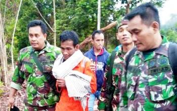 Anggota TNI dari Kodim 1013/Muara Teweh menggiring Samsudin yang terlihat lemas lantaran tersesat di hutan selama tiga hari.