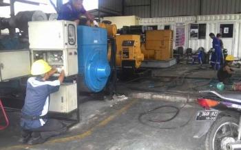 Petugas PLN sedang memperbaiki mesin.
