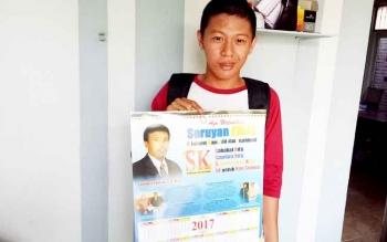 Seorang warga Kuala Pembuang tengah menunjukan kalender 2017 berisikan tentang Sarbinnor Karim.