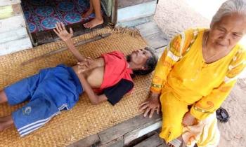 Johan, warga Pematang Kambat Jalan Manggis RT 01 Desa Pematang Panjang, saat terbaring lemah di teras depan rumahnya, ditemani tetangganya, Muliana (60).