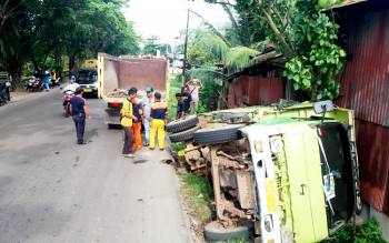 Sejumlah petugas kebersihan bersama para sopir truk berkoordinasi mencari cara untuk mengevakuasi truk yang tumbang di di Jalan Pemuda, Kelurahan Sawahan, Kecamatan Mentawa Baru Ketapang, Kabupaten Kotim, Senin (27/3/2017).