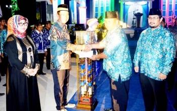 Bupati Barito Utara Nadalsyah menyerahkan piala kepada juara umum STQ ke 48 tingkat kabupaten di malam penutupan, Senin (28/3/2017).