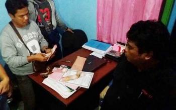 Sejumlah anggota Reskrim sedang memperhatikan tersangka OTT pemerasan yang ditangkap.