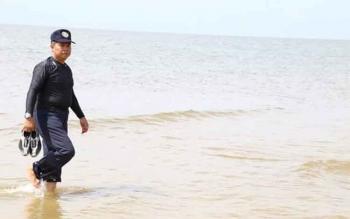 Bupati Seruyan Sudarsono saat menikmati suasana pantai di Desa Sungai Perlu, Kecamatan Seruyan Hilir, belum lama ini.