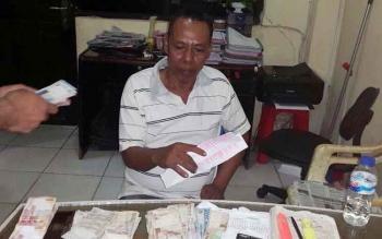 Bandar kupu saat diperiksa di ruang reskrim Polres Kotim, beserta sejumlah barang bukti.