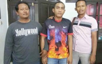 Indra Rukmana (tengah) diapit anggota Polsek Parenggean.