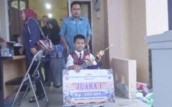 Elvan Yulandi Alfahrezy bersama ayahnya Sukarjudin membawa pulang piala juara pertama Lomba Membaca Tingkat Sekolah Dasar/Sederajat yang dilaksanakan Dinas Kearsipan dan Perpustakaan Kabupaten Murung Raya di Kota Puruk Cahu, Kamis (30/3/2017).