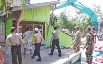 Alat berat merobohkan bangunan di lokalisasi prostitusi Simpang Kodok.