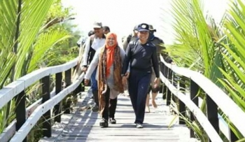 Bupati Seruyan Sudarsono ditemani istrinya Ratna Mustika melintasi jembatan kayu yang ada di Desa Sungai Perlu, Kecamatan Seruyan Hilir, dalam kunjungannya, belum lama ini.
