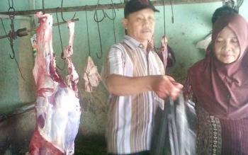 Penjual daging sapi di Pasar Kasongan Kabupaten Katingan sibuk melayani pembeli, Minggu (2/4/2017).