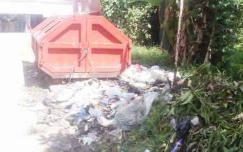 Tampak sampah berhamburan di luar tempat pembuangan sampah.