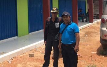 Ketua BPD Umpang, Udin (kiri) berdiri bersama salah satu perangkat desa di depan bangunan pasar desa yang didanai dari Dana Desa tahun 2016.