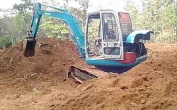 Operator alat berat mini sedang meratakan tanah. Warga Desa Umpang akan membeli alat berat serupa untuk pembukaan lahan.