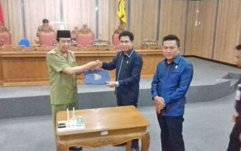Penyerahan draf pengesahan Perda Pilkades, oleh Ketua DPRD Kotim Jhon Krisli kepada Wakil Bupati Kotim HM Taufiq Mukri.