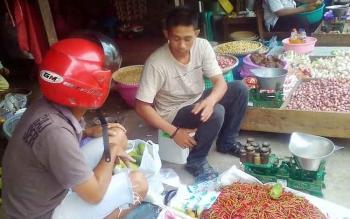 Pedagang cabai Rahmad saat melayani pembeli di pasar tradisional Kapuas, Jalan Mawar, Rabu (5/4/2017).