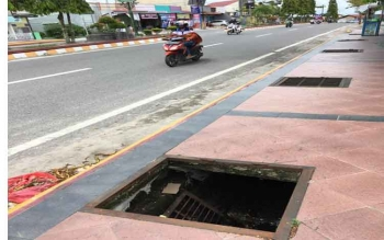 Besi penutup lubang plangson di Jalan Hasanuddin lepas dan masuk ke dalam parit. Lubang menganga tersebut membahayan bagi pejalan kaki.