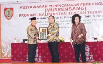 Menteri PPN/Kepala Bappenas Bambang PS Brodjonegoro menerima cinderamata dari Gubernur Kalteng Sugianto Sabran seusai membuka Musrenbang RKPD 2018 Kalteng di Aula Jayang Tingang, Kota Palangka Raya, Kamis (6/4/2017).