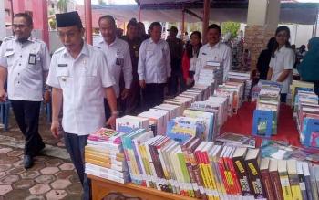 Pj Bupati Barsel, Mugeni melihat buku diperpustakaan pada saat launching. Dihalaman kantor perpustakaan, Rabu 4/4/2017 kemarin.