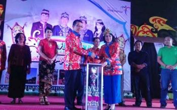 Bupati Murung Raya Perdie M Yoseph menyerahkan piala bergilir kepada Ketua Panitia Festival Budaya Tira Tangka Balang, Regita saat acara pembukaan di Gedung Futsal Tana Malai Tolung Lingu, Kamis (6/4/2017) malam.