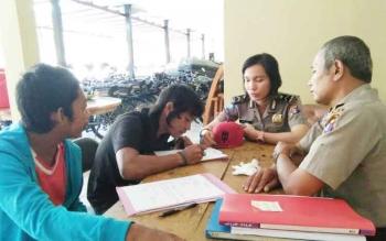 Dua orang anggota Satbinmas Polres Kotim sedang memeriksa dua orang anak funk yang ditangkap mereka pada Jumat (7/4/2017).