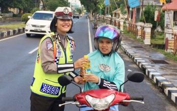 Anggota Satlantas Polres Sukamara membagikan sembako bagi pengendara taat aturan lalu lintas.