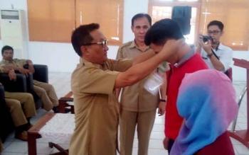 Kepala Dispora Kalteng, Suyanto mengalungkan tanda peserta pelatihan pemuda wirausaha 2017 di aula Bapelkes jalan Yos Sudarso, Selasa (1142017)