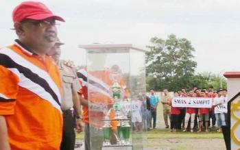 Plt Kepala Dinas Pemuda dan Olahraga Kotawaringin Timur, Najmi Fuadi di samping piala yang akan diperebutkan tim kesebelasan yang mengikuti turnamen Piala Bupati Kotim.