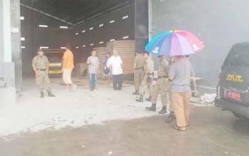 Sejumlah warga saat di gudang Jaya Bangunan milik Rustanto yang dikawal ketat petugas Satpol PP